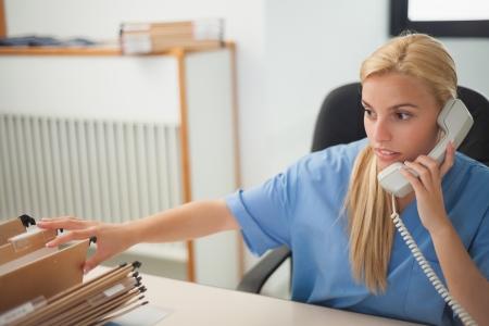 recepcionista: Enfermera que sostiene un tel�fono mientras se busca una carpeta en la recepci�n del hospital Foto de archivo