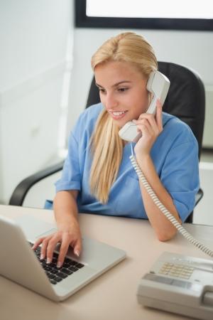 dialing: Enfermera escribiendo en un ordenador port�til mientras est� sosteniendo un tel�fono en recepci�n del hospital