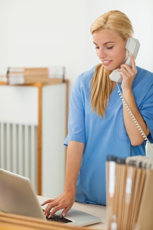 Blonde nurse calling while using a laptop in hospital reception Stock Photo - 16205069