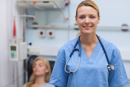 Nurse standing while looking at camera in hospital ward photo