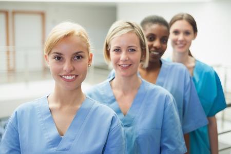 nurses: Female nurse looking at camera in hospital hallway Stock Photo