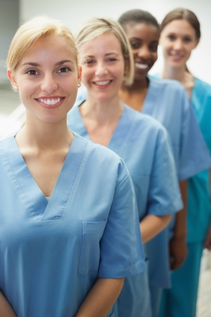 Smiling female nurses looking at camera in hospital hallway photo