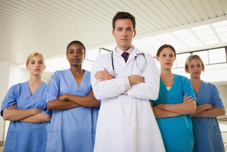 Doctor and nurses with arms crossed in hospital corridor photo