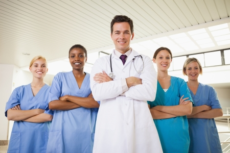 Smiling doctor and nurses with arms crossed in hospital corridor Stock Photo - 16205282