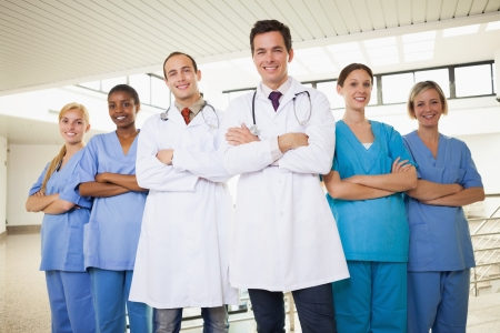 nurse practitioner: Doctors with nurses with arms crossed in hospital corridor
