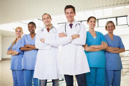 pielęgniarki: Lekarze z pielęgniarek z rękami skrzyżowanymi na korytarzu szpitalnym