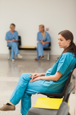 Intern waiting on a chair in hospital waiting room photo