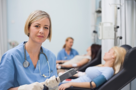 transfused: Nurse holding a clipboard next to a transfused patient in hospital ward Stock Photo