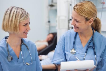 female nurse: Smiling nurses talking in hospital ward Stock Photo