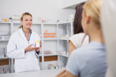 Smiling pharmacist holding on her hands a box in hospital ward photo