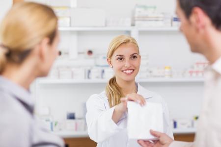 drugstore: Sonriendo farmacéutico dando una bolsa de droga en una farmacia Foto de archivo