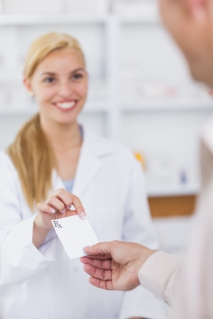 Patient giving a prescription to a pharmacist in a pharmacy photo