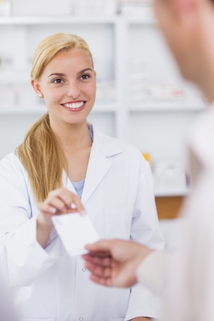 pharmacist: Patient giving a prescription to a smiling pharmacist in hospital