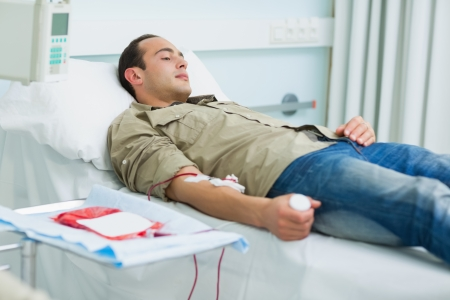 Transfused patient lying on a bed in hospital ward photo