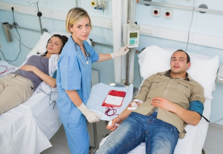 Nurse touching monitor next to transfused patients in hospital ward photo