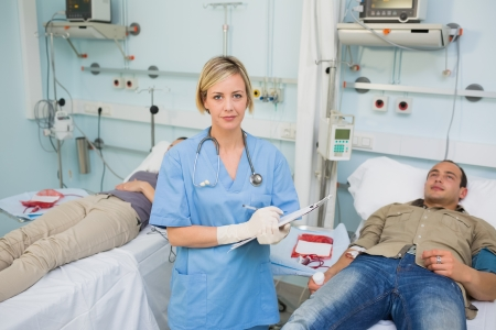 transfused: Nurse holding a clipboard next to transfused patients in hospital ward Stock Photo