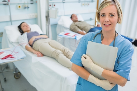 Nurse standing next to transfused patients in hospital ward Stock Photo - 16207158