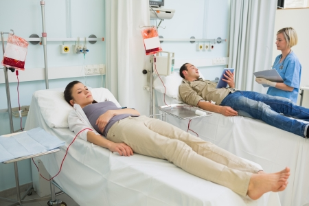 transfused: Two transfused patients lying on a medical bed in hospital ward