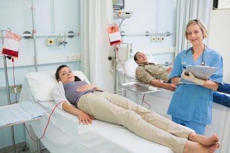 transfused: Transfused patients next to a nurse in hospital ward