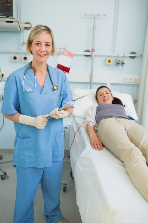 Nurse holding a clipboard while standing in hospital\ ward