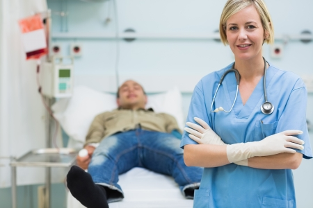Nurse next to a male patient with arms crossed in hospital ward photo