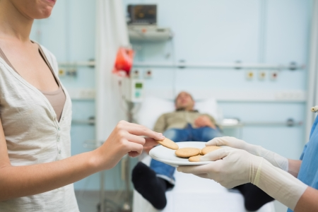 Nurse giving biscuits to a donor in hospital ward photo