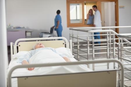 hospital corridor: Elderly patient sleeping in hospital hallway