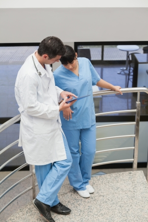Doctor showing someting to a nurse in hospital stairs photo
