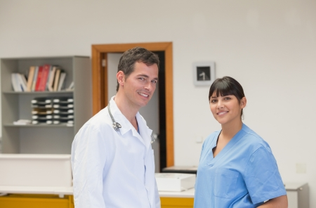 Doctor and a nurse smiling in hospital reception photo