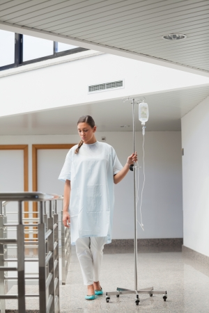 Female patient walking while holding a drip stand in hospital ward photo