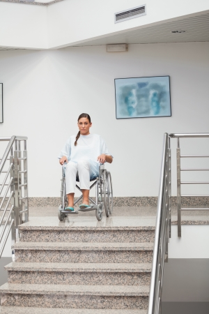 hospitalized: Female patient sitting on a wheelchair in hospital corridor