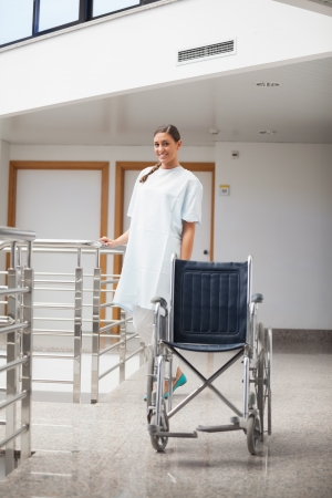 Smiling patient standing next to a wheelchair in hospital hallway photo
