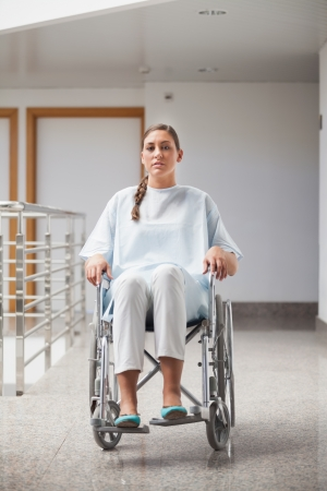 Front view of a patient sitting on a wheelchair in hospital hallway photo