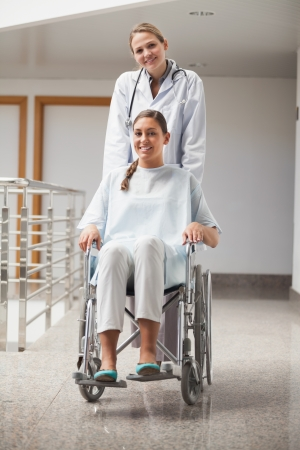 Doctor and patient looking at camera in hospital hallway Stock Photo - 16205302