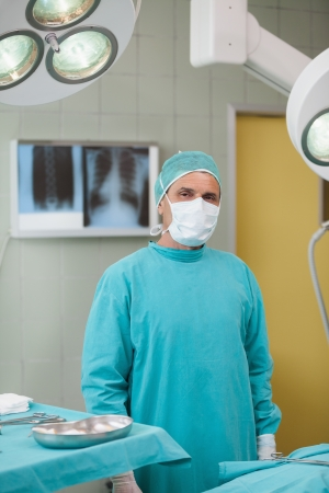 Serious surgeon standing in operating theater photo
