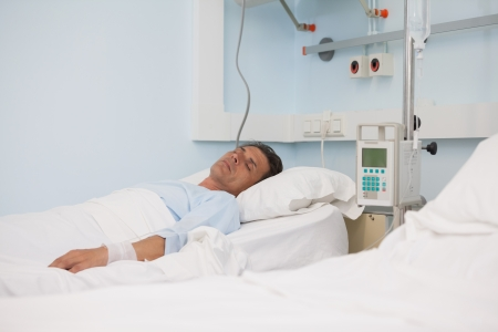hospital patient: Asleep patient on a medical bed in hospital ward