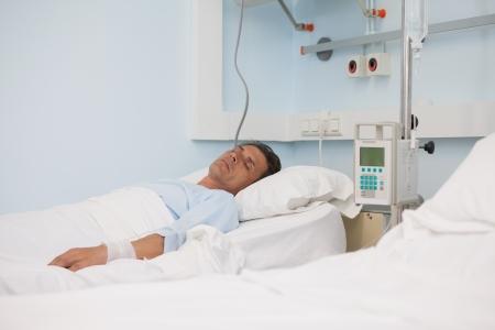 recovery bed: Paziente addormentato su un letto medico in reparto ospedaliero