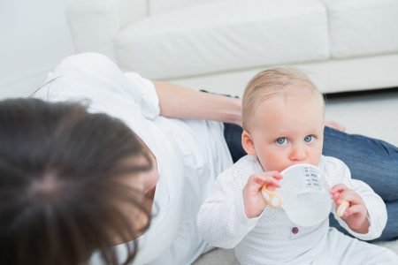 Baby drinking a bottle of water in living room photo