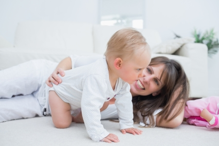 Baby on all fours next to his mother in living room Stock Photo - 16204272