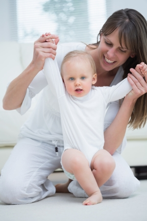 Mother raising arms of her baby in living room Stock Photo - 16207214