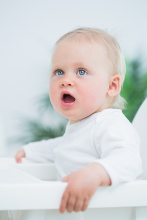 Baby sitting on a high chair in living room Stock Photo - 16202320