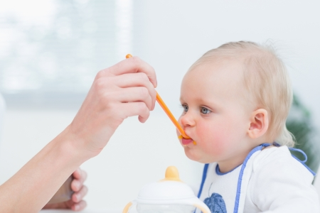 Baby with a plastic spoon on his mouth in living room Stock Photo - 16202718