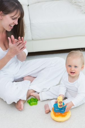 Baby sitting on the floor while playing in living room Stock Photo - 16206932
