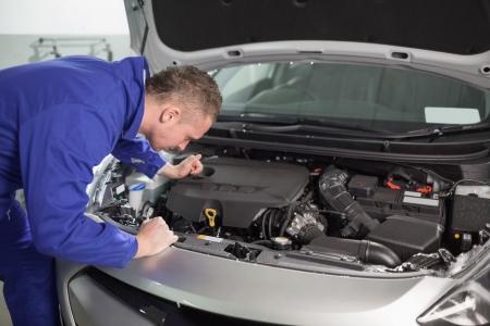 Mec�nico mirando el motor de coche en un garaje photo