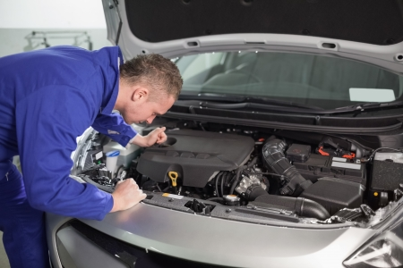 Mechanic looking at an engine of car in a garage Stock Photo - 16208146