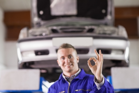 Smiling mechanic doing a gesture with his fingers in a garage photo