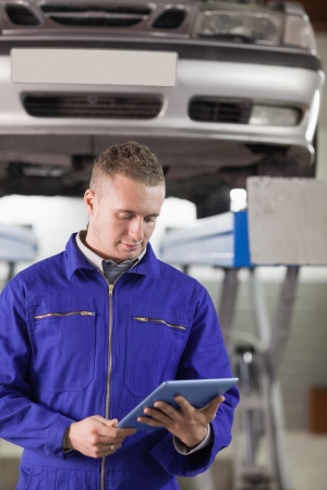 car transmission: Mechanic looking at a tablet computer while holding it in a garage