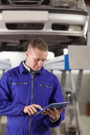 Konzentrierte Mechaniker h�lt einen Tablet-Computer in einer Garage