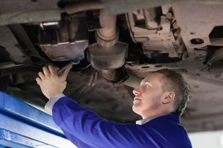 gudgeon: Mechanic repairing the below of a car in a garage