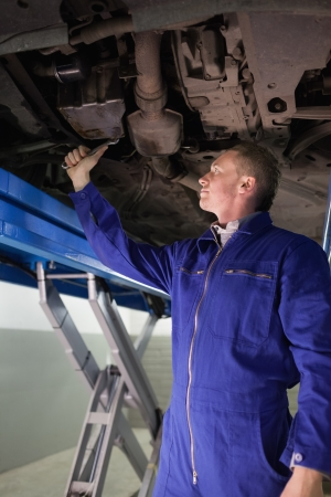 gudgeon: Mechanic repairing with a spanner the below of a car in a garage